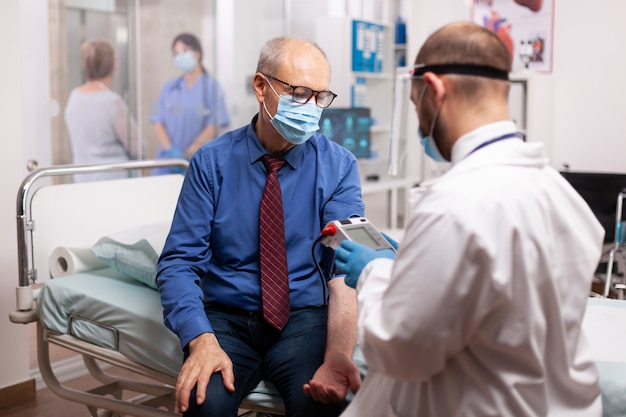 Medico che misura la pressione sanguigna del paziente anziano nella sala di consultazione dell'ospedale durante l'esame covid19