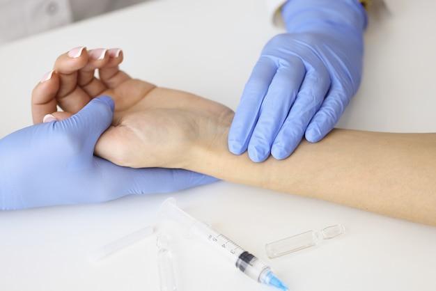 Medico che misura l'impulso sull'avambraccio del paziente vicino alla siringa vuota e al primo piano del farmaco