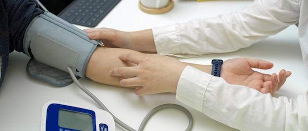 Aggiusti il controllo medico il suo paziente con il monitor di pressione sanguigna nella stanza dell'esame
