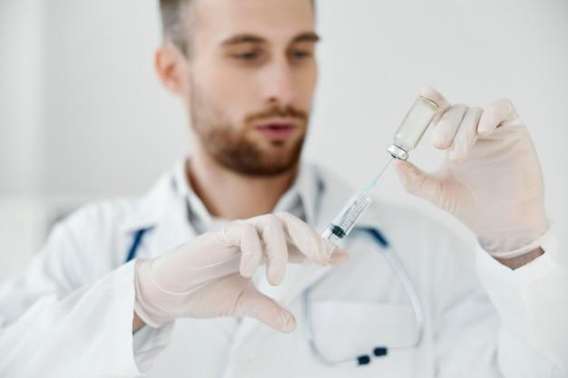Il dottore in camice medico tiene una siringa in mano e un'iniezione di vaccino