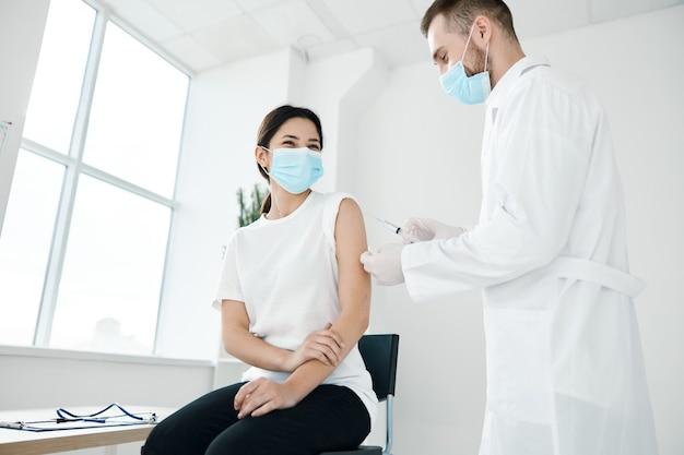 Dottore in un camice medico e una donna in una maschera protettiva