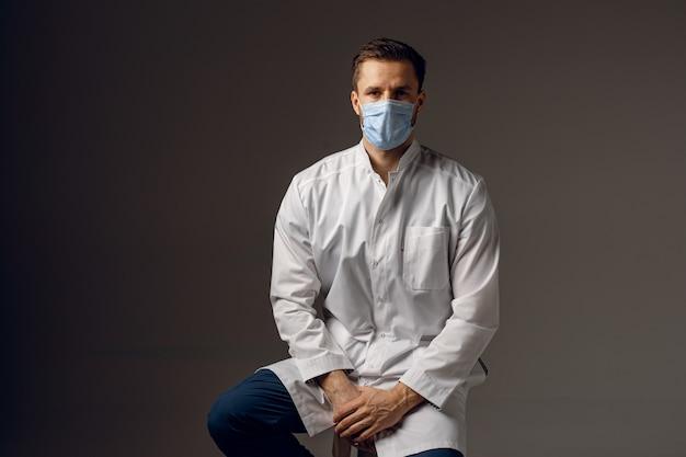 Dottore in maschera medica per la protezione contro il covid-19. bello uomo con indosso una veste medica