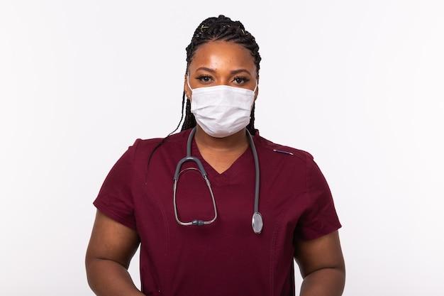 Dottore in una mascherina medica sul muro bianco