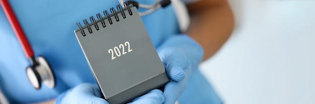 Dottore in guanti di gomma medica che tiene il calendario da tavolo per il primo piano