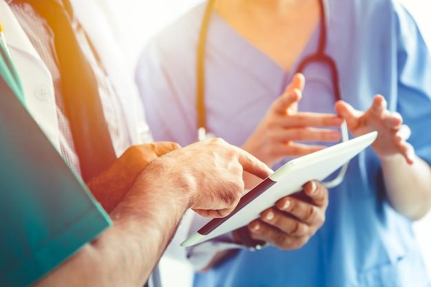 Discussione del team medico medico sul caso del paziente utilizzando lo schermo del monitor del computer palmare o tablet
