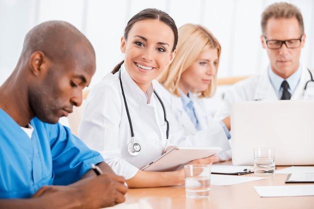 Dottore in riunione. bella giovane dottoressa che sorride mentre è seduta insieme ai suoi colleghi alla riunione