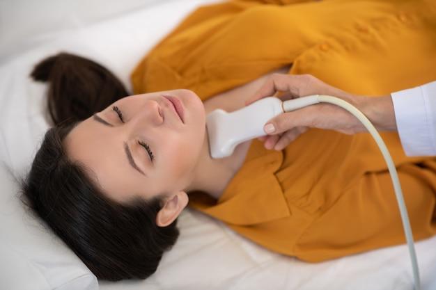 Medico in movimento sensore a ultrasuoni sulla ghiandola tiroidea dei pazienti