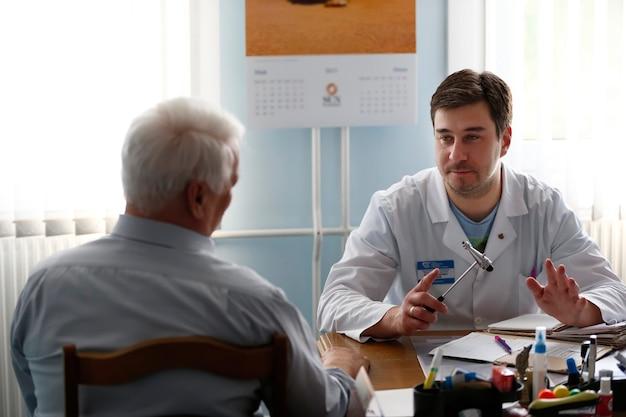 Il medico neurologo prende il paziente. accoglienza dal medico degli anziani. nell'ufficio del medico