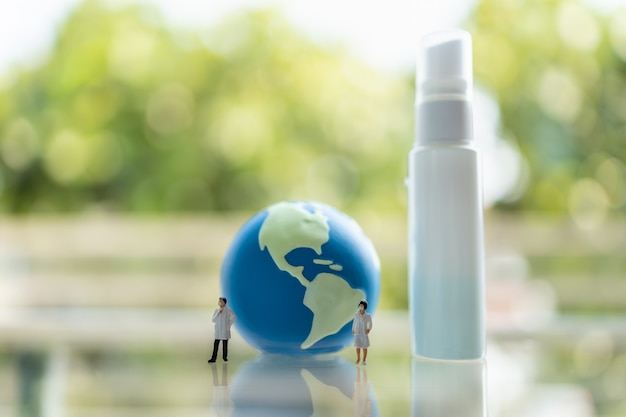 Figura in miniatura di dottore e infermiere con maschera facciale in piedi con palla mondiale e bottiglia di alcol spray