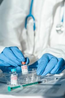 Medico o infermiere in tuta protettiva con vaccino covid 19 e placebo