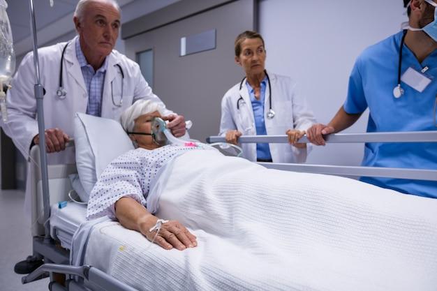 Medico ed infermiere che spingono il letto della barella di emergenza in corridoio