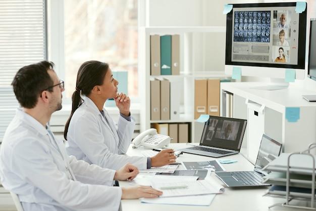 Medico e infermiere seduti al tavolo e ascoltando i loro colleghi sul monitor del computer hanno una conferenza online