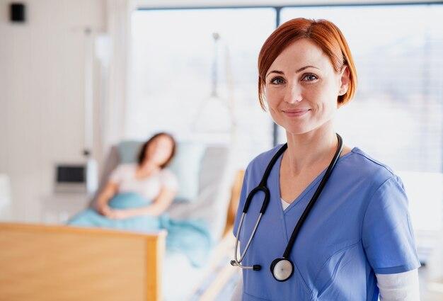 Un medico o un'infermiera in piedi nella stanza d'ospedale, guardando la fotocamera. copia spazio.