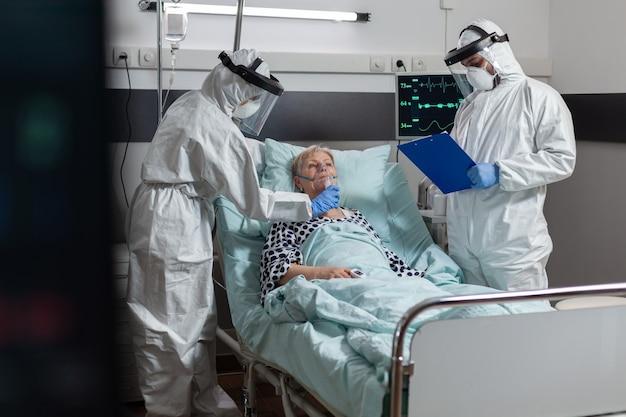 Il medico e l'infermiera che indossano coprono tutte le tute in dpi come prevenzione
