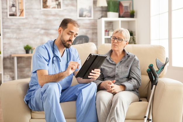 Dottore in casa di cura utilizzando computer tablet durante l'assunzione con pensionato femminile.