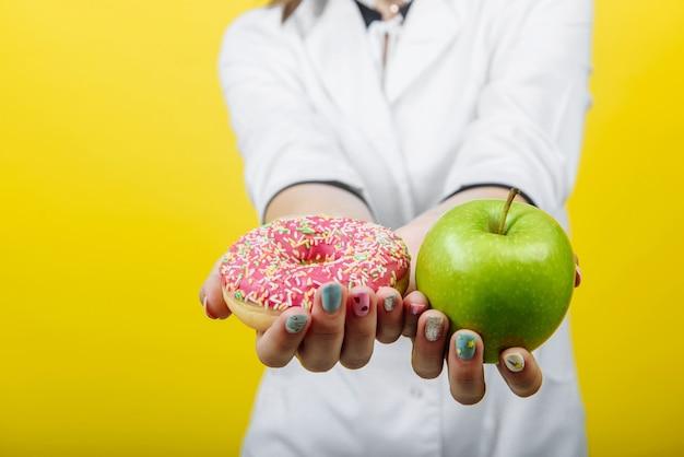 Medico nutrizionista che tiene una ciambella di zucchero e una mela verde. il concetto di confronto dietetico. posto libero