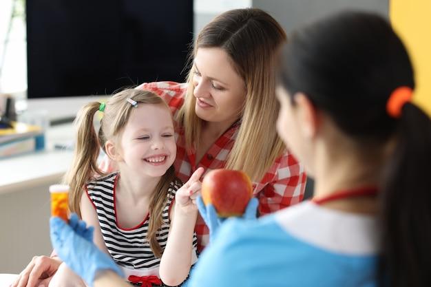 Medico che offre bambina bottiglia di medicina e mela rossa in clinica