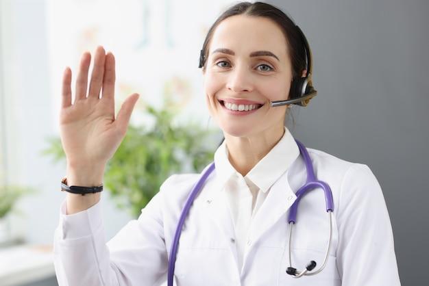 Operatore medico nel call center tiene la mano in segno di saluto
