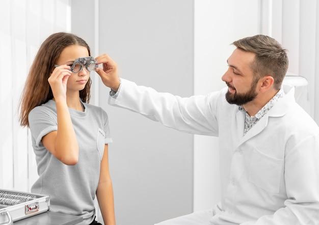 Medico oculista che tiene attrezzatura esaminando gli occhi delle ragazze dell'adolescente nella clinica