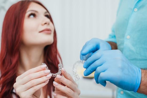 Il medico ortodontista consiglia a una ragazza gli allineatori in silicone per raddrizzare i denti