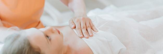 Le mani del dottore osteopata fanno terapia fisiologica ed emotiva per una bambina di otto anni. sessione di trattamento di osteopatia pediatrica. medicina alternativa. prendersi cura della salute del bambino. striscione