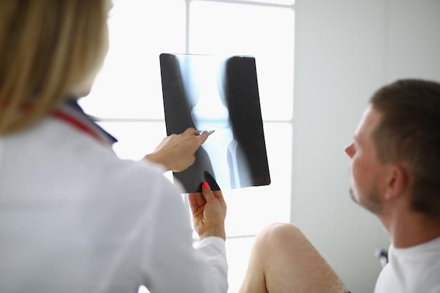 Il medico e il paziente stanno esaminando i raggi x.