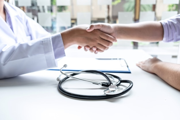 Medico e paziente si stringono la mano dopo aver controllato con la consultazione e la diagnosi al trattamento