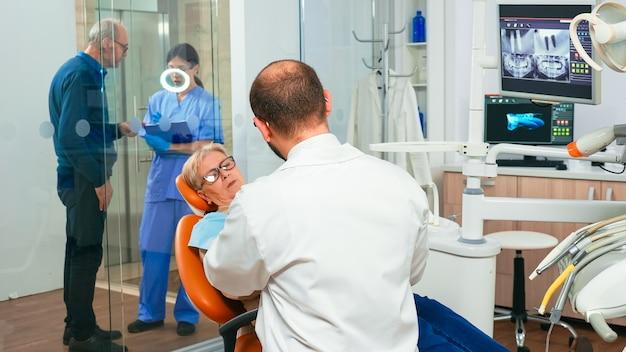 Medico e paziente che parlano di problemi con la dentiera dell'anziana dentista e infermiere che lavorano insieme nel moderno ufficio stomatologico spiegando la radiografia dentale dal monitor digitale in background