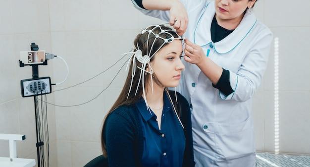 Medico e paziente con elettrodo per encefalografia.