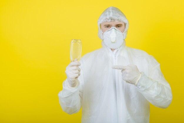 Un medico in una tuta protettiva personale (dpi) tiene tra le mani una bottiglia di disinfettante indossa una maschera medica e guanti. isolato. sfondo giallo