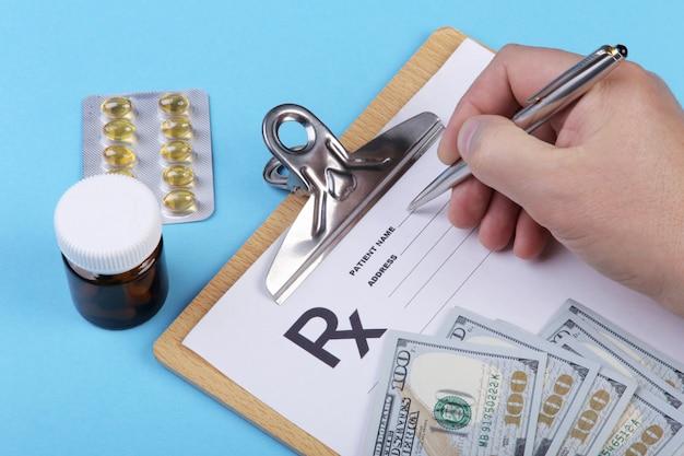 Medico o farmacista tenendo il barattolo o una bottiglia di pillole in mano su uno sfondo di banconote in dollari e scrivendo la prescrizione su un modulo speciale. spese mediche e concetto di pagamento sanitario.