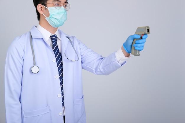 Medico medico che misura la temperatura corporea con la pistola a infrarossi termometro frontale