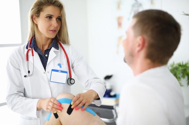 Medico fisioterapista che attacca i nastri sull'uomo dolorante al ginocchio