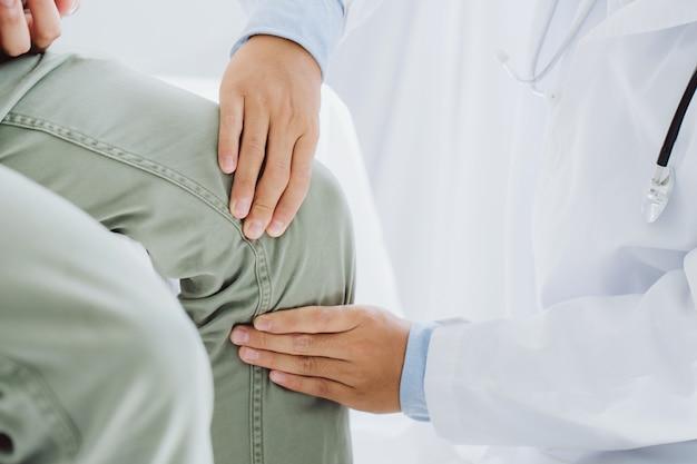 Medico fisioterapista che lavora esaminando il trattamento del ginocchio infortunato del paziente, usando la maniglia del ginocchio del paziente per controllare il dolore.