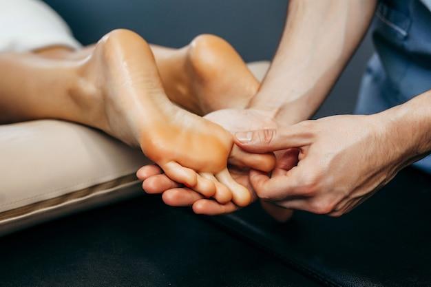 Il medico-podologo esegue un esame e un massaggio del piede del paziente in clinica.