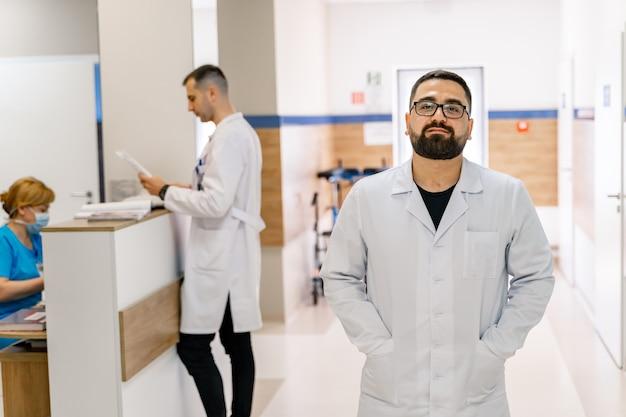 Ritratto del medico sullo sfondo del corridoio dell'ospedale. ritratto del medico in camice. dottore barbuto.