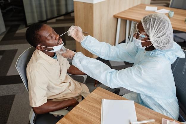 Dottore in tuta dpi che raccoglie muco nasale con tampone per testare l'infezione da covid