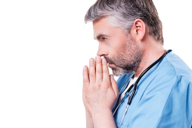 Dottore che prega. vista laterale del medico maturo dei capelli grigi che si tiene per mano stretta vicino al viso mentre si trova in piedi isolato su bianco
