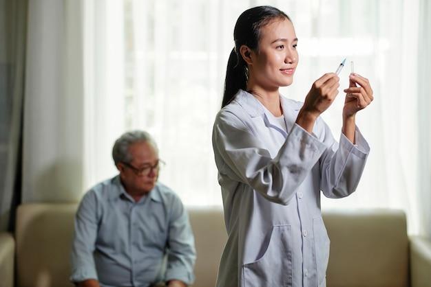 Medico che prepara il vaccino per l'uomo anziano