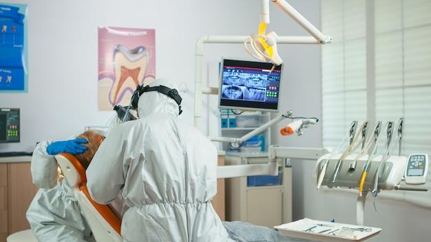 Medico in tuta protettiva che utilizza la perforatrice durante l'esame odontoiatrico in periodo di pandemia. ortodontista e infermiere che lavorano indossando tuta, visiera, maschera, guanti in ufficio stomatologico