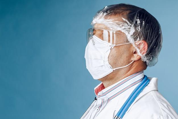 Dottore in abbigliamento protettivo su sfondo blu. avvicinamento
