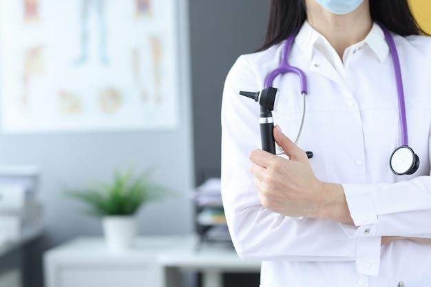 Il dottore in maschera protettiva tiene un otoscopio nelle sue mani. visita medica al concetto di laura
