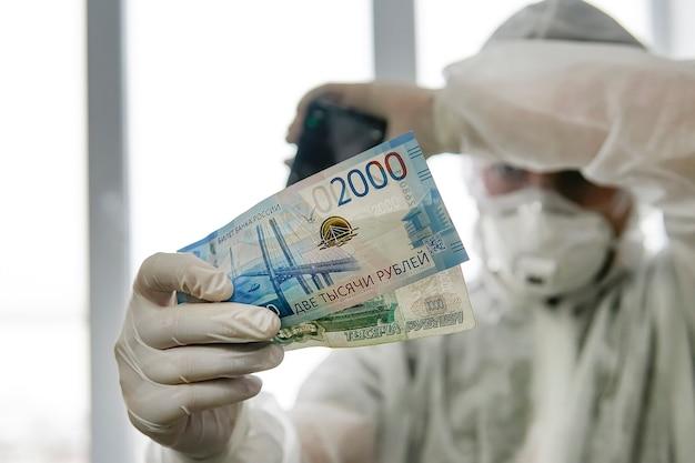Il dottore con una maschera protettiva e una tuta a prova di virus in ospedale conta i soldi. pagamento ai dipendenti in zona rossa. un lavoro pericoloso con uno stipendio basso. premio ai medici che lavorano con i pazienti covid