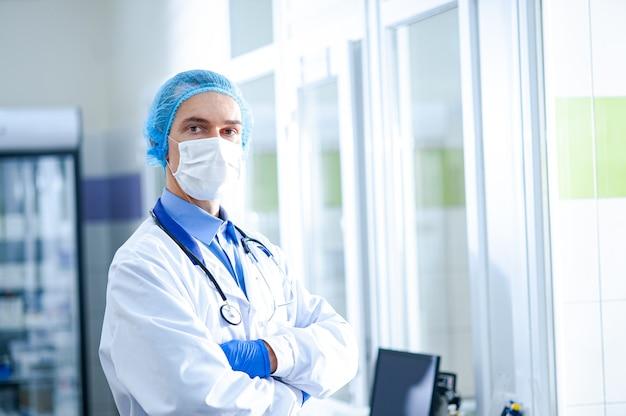 Un medico con una maschera protettiva con un fonendoscopio si trova in ospedale. concetto di salute. epidemia di coronavirus