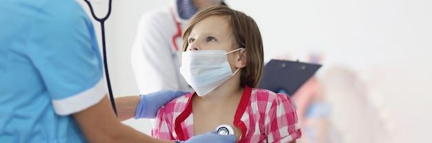 Medico della maschera medica protettiva che ascolta il cuore con lo stetoscopio alla bambina