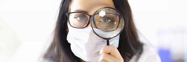 Il dottore in maschera medica protettiva guarda attraverso la lente d'ingrandimento. cerca il concetto di prodotti medicinali