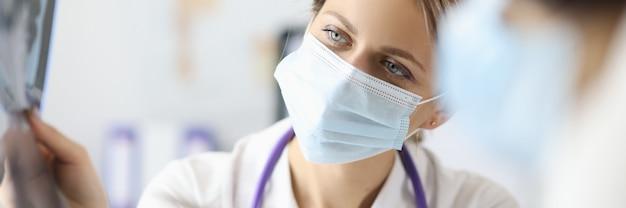 Medico nella mascherina medica protettiva che mostra la penna sui raggi x in clinica