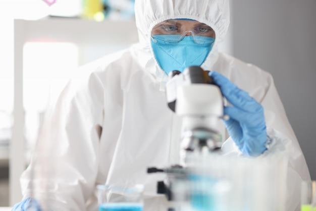 Il dottore in tuta medica protettiva, maschera e occhiali guarda attraverso il microscopio. ricerca medica