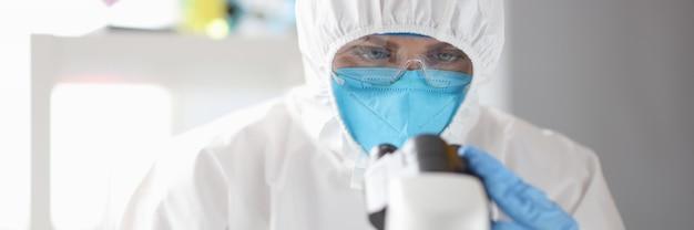 Il dottore in tuta medica protettiva maschera e occhiali guarda attraverso la ricerca medica al microscopio