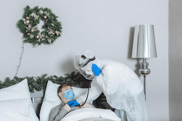 Il dottore in una tuta protettiva in ppe ascolta un paziente con uno stetoscopio a casa prima del nuovo anno e del natale